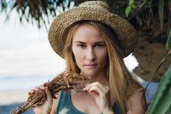 Νέα γυναίκα στην ανθοδέσμη λαβής καπέλων αχύρου των ξηρών wildflowers στοκ εικόνα με δικαίωμα ελεύθερης χρήσης