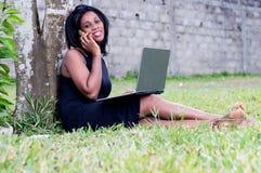 Νέα γυναίκα στην επικοινωνία στο πάρκο στοκ φωτογραφία