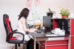 Νέα γυναίκα στην εργασία ως ρεσεψιονίστ Στοκ Εικόνες