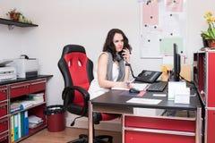 Νέα γυναίκα στην εργασία ως ρεσεψιονίστ Στοκ Φωτογραφίες