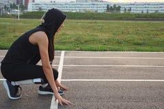 Νέα γυναίκα στην κουκούλα στην αρχική γραμμή μιας διαδρομής σταδίων που προετοιμάζεται για ένα τρέξιμο στοκ φωτογραφίες με δικαίωμα ελεύθερης χρήσης
