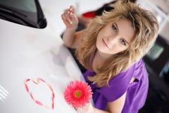Νέα γυναίκα στην κουκούλα του νέου αυτοκινήτου με το λουλούδι και το κατοικίδιο ζώο Στοκ Εικόνα