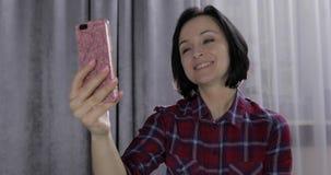 Νέα γυναίκα στην κρεβατοκάμαρα που απολαμβάνει έχοντας την τηλεοπτική συνομιλία που χρησιμοποιεί το smartphone απόθεμα βίντεο