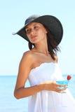 Νέα γυναίκα στην παραλία με το κοκτέιλ Στοκ Εικόνες