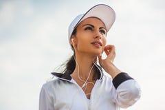Νέα γυναίκα στην παραλία που ακούει τη μουσική Στοκ Φωτογραφίες