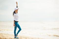 Νέα γυναίκα στην παραλία που ακούει τη μουσική Στοκ εικόνες με δικαίωμα ελεύθερης χρήσης