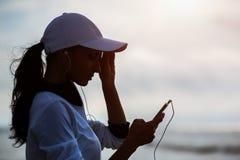 Νέα γυναίκα στην παραλία που ακούει τη μουσική Στοκ φωτογραφίες με δικαίωμα ελεύθερης χρήσης