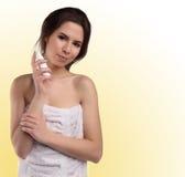 Νέα γυναίκα στην πετσέτα λουτρών με το μπουκάλι κρέμας, που απομονώνεται σε κίτρινο Στοκ Εικόνες