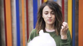Νέα γυναίκα στην πράσινη καραμέλα βαμβακιού κατανάλωσης κοντά σε έναν χρωματισμένο ουράνιο τόξο τοίχο απόθεμα βίντεο