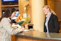 Νέα γυναίκα στην υποδοχή ξενοδοχείων Στοκ Φωτογραφία