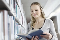 Νέα γυναίκα στη βιβλιοθήκη Στοκ φωτογραφίες με δικαίωμα ελεύθερης χρήσης