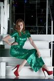 Νέα γυναίκα στη μακροχρόνια πράσινη συνεδρίαση φορεμάτων στα σκαλοπάτια Στοκ Εικόνα