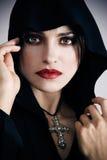 Νέα γυναίκα στη μαύρη κουκούλα με το σταυρό στοκ φωτογραφίες