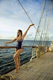 Νέα γυναίκα στη μοντέρνη τοποθέτηση μαγιό αρκετά στη βάρκα πανιών Στοκ Φωτογραφία