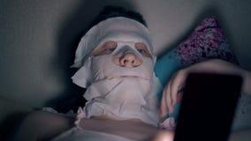 Νέα γυναίκα στη ρόδινη κορυφή με την άσπρη μάσκα φύλλων στο πρόσωπο απόθεμα βίντεο