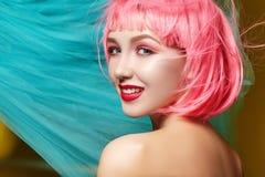 Νέα γυναίκα στη ρόδινη περούκα Όμορφο πρότυπο με τη μόδα makeup Το φωτεινό ελατήριο κοιτάζει Προκλητικό χρώμα τρίχας, μέσο hairst στοκ εικόνα