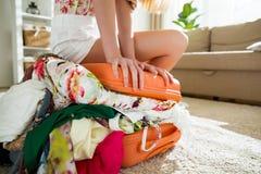 Νέα γυναίκα στη συνεδρίαση μεσημεριανού διαλείμματος επανδρωμένη στην πορτοκάλι βαλίτσα Στοκ Φωτογραφίες