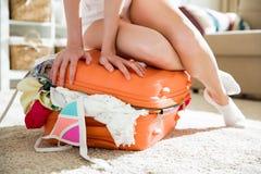 Νέα γυναίκα στη συνεδρίαση μεσημεριανού διαλείμματος επανδρωμένη στην πορτοκάλι βαλίτσα Στοκ Εικόνες