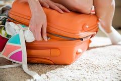 Νέα γυναίκα στη συνεδρίαση μεσημεριανού διαλείμματος επανδρωμένη στην πορτοκάλι βαλίτσα Στοκ Φωτογραφία