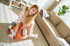 Νέα γυναίκα στη συνεδρίαση μεσημεριανού διαλείμματος επανδρωμένη στην πορτοκάλι βαλίτσα Στοκ εικόνα με δικαίωμα ελεύθερης χρήσης