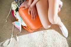 Νέα γυναίκα στη συνεδρίαση μεσημεριανού διαλείμματος επανδρωμένη στην πορτοκάλι βαλίτσα Στοκ φωτογραφίες με δικαίωμα ελεύθερης χρήσης