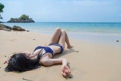 Νέα γυναίκα στη χαλάρωση μπικινιών στην παραλία στοκ εικόνα με δικαίωμα ελεύθερης χρήσης
