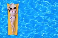 Νέα γυναίκα στη χαλάρωση μπικινιών στην πισίνα στοκ εικόνα με δικαίωμα ελεύθερης χρήσης