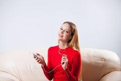 Νέα γυναίκα στη χαλάρωση μουσικής ακούσματος ακουστικών στο σπίτι έτσι Στοκ φωτογραφίες με δικαίωμα ελεύθερης χρήσης