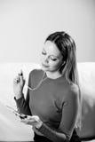 Νέα γυναίκα στη χαλάρωση μουσικής ακούσματος ακουστικών στο σπίτι έτσι Στοκ Εικόνες