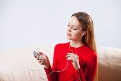 Νέα γυναίκα στη χαλάρωση μουσικής ακούσματος ακουστικών στο σπίτι έτσι Στοκ εικόνα με δικαίωμα ελεύθερης χρήσης