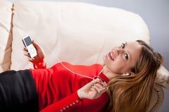 Νέα γυναίκα στη χαλάρωση μουσικής ακούσματος ακουστικών στο σπίτι έτσι Στοκ Εικόνα
