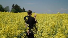 Νέα γυναίκα στις μαύρες φόρμες ενδυμάτων που τρέχουν μέσω του κίτρινου τομέα σχετικά με τα λουλούδια hd απόθεμα βίντεο