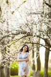 Νέα γυναίκα στον ανθίζοντας κήπο βερίκοκων Στοκ Φωτογραφία