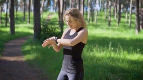 Νέα γυναίκα στον αποφορτιμένος δρόμο φιλάθλων στο θερινό δάσος φιλμ μικρού μήκους