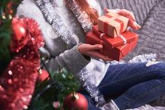 Νέα γυναίκα στον καναπέ με τα χριστουγεννιάτικα δώρα στοκ εικόνα