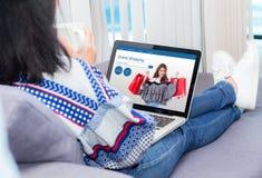 νέα γυναίκα στον καναπέ που ψωνίζει on-line με το σημειωματάριο Στοκ Εικόνες