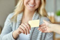 Νέα γυναίκα στον καφέ που δίνει μια πιστωτική κάρτα σε άλλο χέρι Στοκ Φωτογραφία