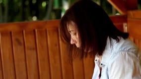 Νέα γυναίκα στον πάγκο που κοιτάζει στο τηλέφωνο κυττάρων απόθεμα βίντεο