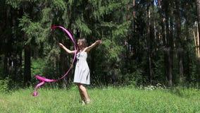 Νέα γυναίκα στους γκρίζους χορούς φορεμάτων με την κορδέλλα στο θερινό δάσος απόθεμα βίντεο