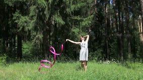 Νέα γυναίκα στους χορούς φορεμάτων με τη ρόδινη κορδέλλα φιλμ μικρού μήκους