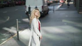 Νέα γυναίκα στο άσπρο παλτό που περπατά στην οδό και που κυματίζει στη κάμερα απόθεμα βίντεο