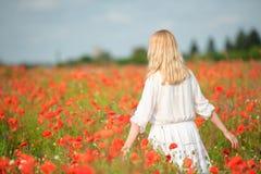 Νέα γυναίκα στο άσπρο περπάτημα σε έναν τομέα των παπαρουνών στοκ φωτογραφία