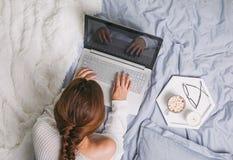 Νέα γυναίκα στο άσπρο πουλόβερ που βρίσκεται στο κρεβάτι και που χρησιμοποιεί το lap-top στοκ εικόνες