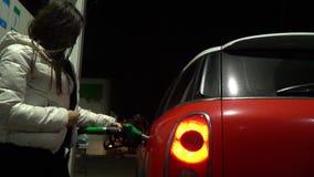 Νέα γυναίκα στο άσπρο σακάκι, που καλύπτει από τον αέρα τροφοδοτώντας με καύσιμα το αυτοκίνητό της απόθεμα βίντεο