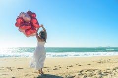 Νέα γυναίκα στο άσπρο φόρεμα με τα κόκκινα μπαλόνια στην παραλία Στοκ εικόνα με δικαίωμα ελεύθερης χρήσης