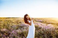 Νέα γυναίκα στο γαμήλιο φόρεμα υπαίθρια Όμορφη νύφη σε έναν τομέα στο ηλιοβασίλεμα στοκ εικόνες