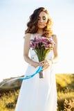 Νέα γυναίκα στο γαμήλιο φόρεμα υπαίθρια Όμορφη νύφη σε έναν τομέα στο ηλιοβασίλεμα Στοκ Φωτογραφία
