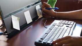 Νέα γυναίκα στο γραφείο που γράφει στην αυτοκόλλητη ετικέττα που κολλιέται στο όργανο ελέγχου απόθεμα βίντεο