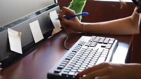 Νέα γυναίκα στο γραφείο που γράφει στην αυτοκόλλητη ετικέττα που κολλιέται στο όργανο ελέγχου φιλμ μικρού μήκους