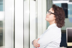 Νέα γυναίκα στο γραφείο που εξετάζει το παράθυρο Στοκ εικόνες με δικαίωμα ελεύθερης χρήσης